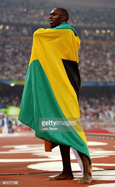 Usain Bolt of Jamaica celebrates with his countries flag after breaking the world record with a time of 1930 to win the gold medal in the Men's 200m...