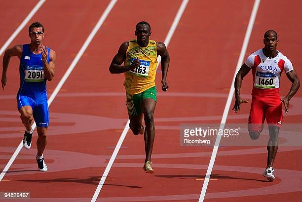 Usain Bolt of Jamaica center Fabio Cerutti of Italy left and Jenris Vizcaino of Cuba run in the first heat of the men's 100meter Athletics event on...
