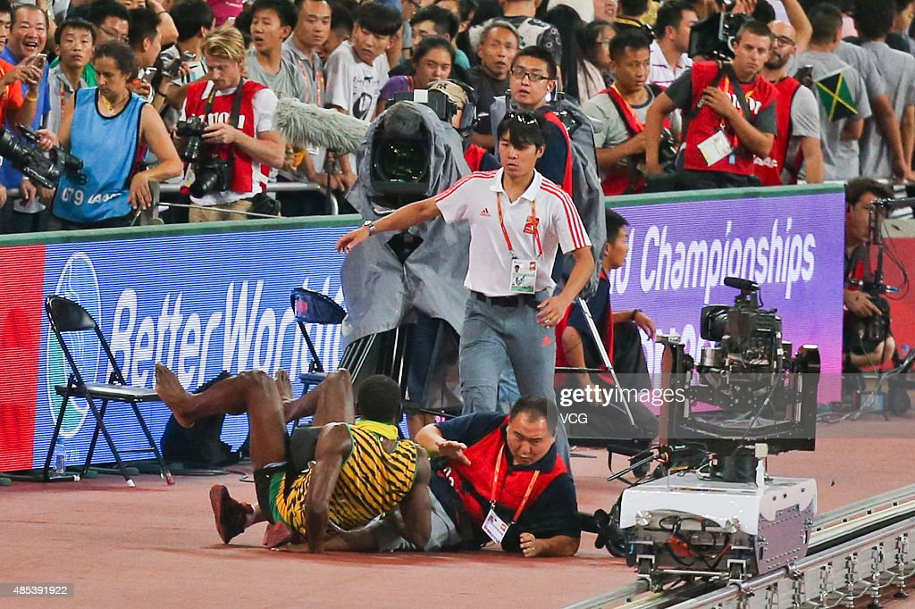 Usain Bolt of Jamaica collides with a worker as he celebrates after winning gold in the Men's 200 metres final during day six of the 15th IAAF World Athletics Championships Beijing 2015 at Beijing National Stadium on August 27, 2015 in Beijing, China.