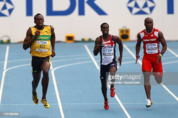 Usain Bolt of Jamaica competes with Christian Malcolm of Great Britain and Emmanuel Callender of Trinidad & Tobago in the men's 200 metres heats...