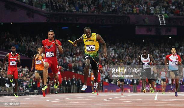 Usain Bolt of Jamaica crosses the finish line ahead of Ryan Bailey of the United States to win gold and set a new world record of 3684 during the...