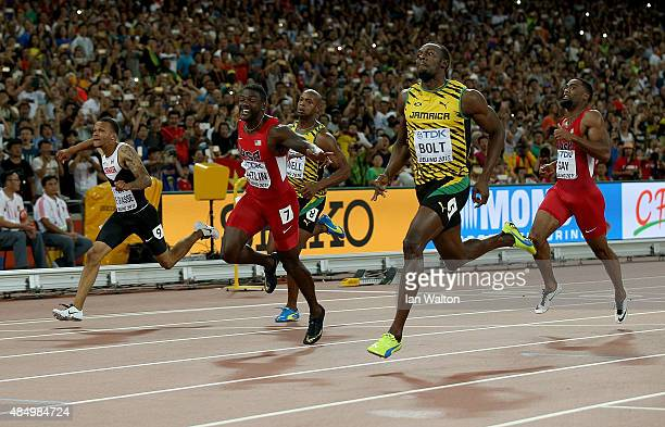 Usain Bolt of Jamaica crosses the finish line to win gold in the Men's 100 metres final as Justin Gatlin of the United States wins silver during day...