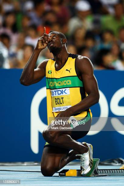 Usain Bolt of Jamaica gestures to the sky prior to competing in the men's 200 metres semi finals during day seven of 13th IAAF World Athletics...