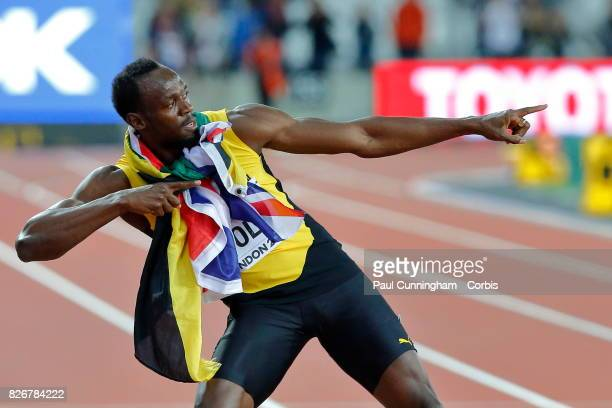 Usain Bolt of Jamaica having run his last 100m race stands with both the Jamaican and Union Jack flag around his neck and pulls into his famous...