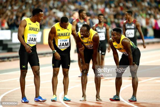 Usain Bolt of Jamaica is attended to by teammmates Yohan Blake, Julian Forte and Omar McLeod after falling in the Men's 4x100 Relay final during day...