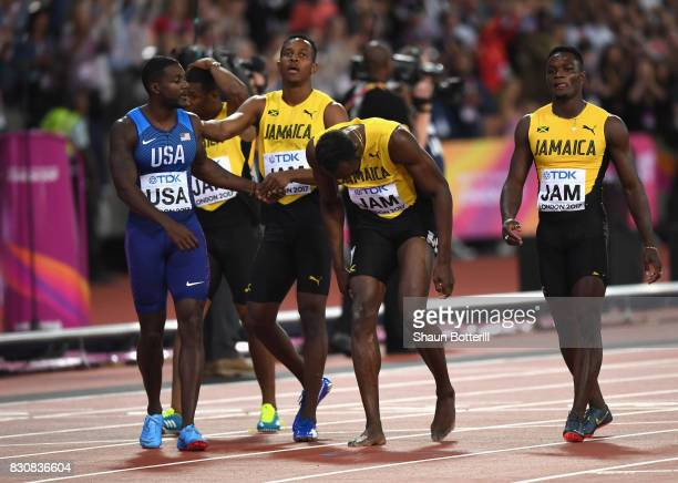 Usain Bolt of Jamaica is attended to by teammmates Yohan Blake Julian Forte and Omar McLeod and Justin Gatlin of the United States after falling in...