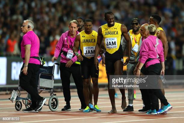 Usain Bolt of Jamaica is helped up by teammates after falling in the Men's 4x100 Relay final during day nine of the 16th IAAF World Athletics...