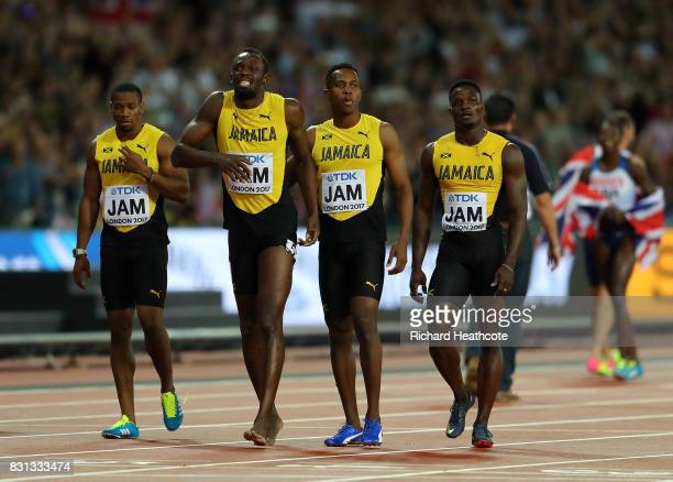 Usain Bolt of Jamaica is joined by teammmates Yohan Blake, Julian Forte and Omar McLeod after falling in the Men's 4x100 Relay final during day nine...