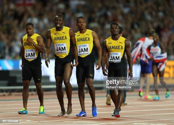 Usain Bolt of Jamaica is joined by teammmates Yohan Blake Julian Forte and Omar McLeod after falling in the Men's 4x100 Relay final during day nine...