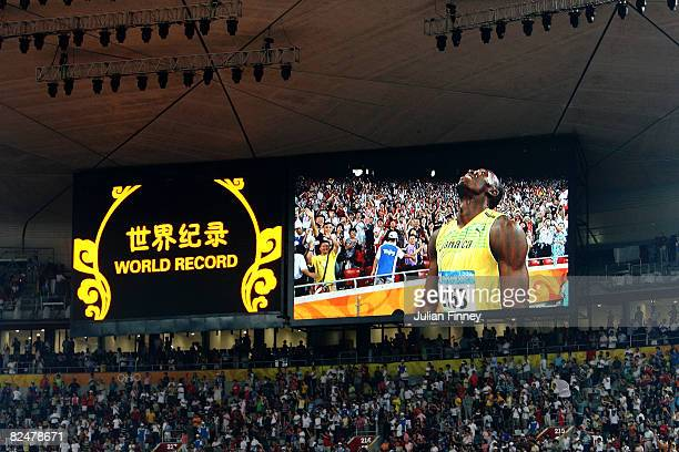 Usain Bolt of Jamaica is seen on the jumbotron as he reacts after breaking the world record with a time of 19.30 to win the gold medal in the men's...