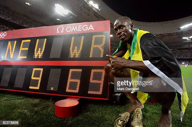 Usain Bolt of Jamaica poses by the clock displaying his winning time after the Men's 100m Final at the National Stadium on Day 8 of the Beijing 2008...