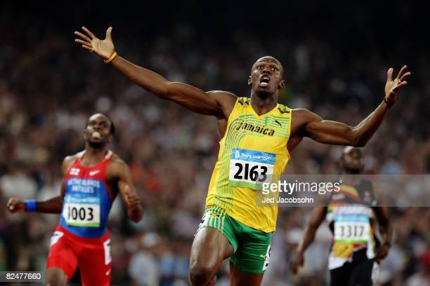 Usain Bolt of Jamaica reacts after breaking the world record with a time of 1930 to win the gold medal as Churandy Martina of Netherlands Antilles...