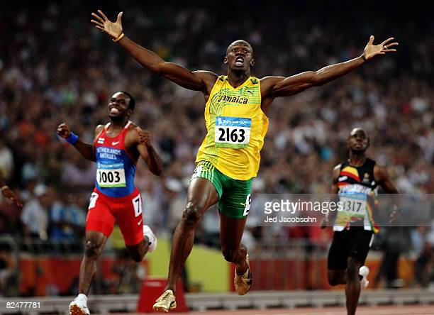 Usain Bolt of Jamaica reacts after breaking the world record with a time of 19.30 to win the gold medal as Churandy Martina of Netherlands Antilles...