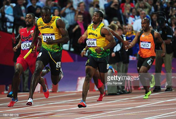 Usain Bolt of Jamaica receives the relay baton from Yohan Blake of Jamaica next to Tyson Gay of the United States during the Men's 4 x 100m Relay...