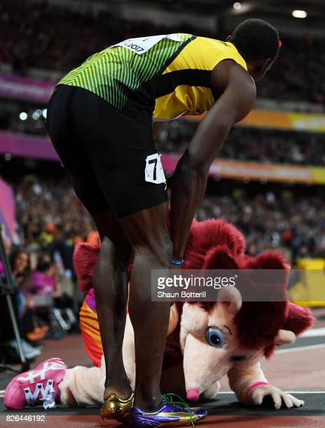 Usain Bolt of Jamaica shares a joke with Hero event mascot the hedgehog following the Men's 100 metres heats during day one of the 16th IAAF World...