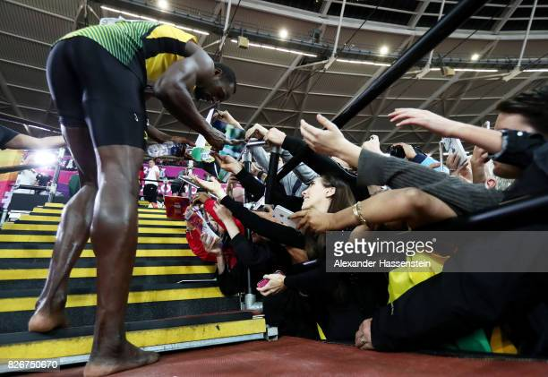 Usain Bolt of Jamaica signs autographs during a lap of honour following finishing in third place in the mens 100m final during day two of the 16th...