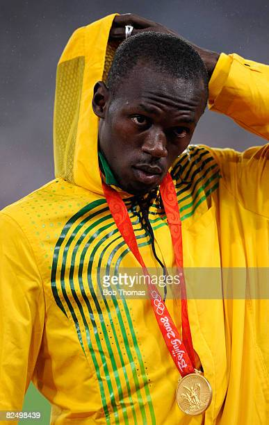 Usain Bolt of Jamaica stands on the podium with his gold medal during the medal ceremony for the Men's 200m Final held at the National Stadium during...