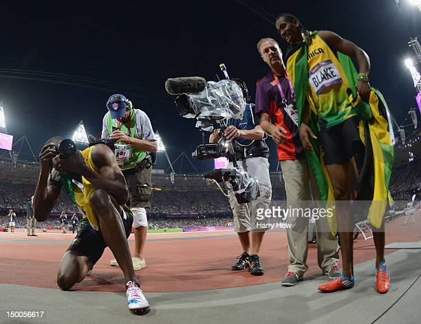 Usain Bolt of Jamaica takes photographs of photographers with one of their cameras as he celebrates winning gold in the Men's 200m Final next to...