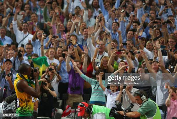 Usain Bolt of Jamaica takes photographs of the crowd with one of the photographers' cameras as he celebrates winning gold in the Men's 200m Final on...