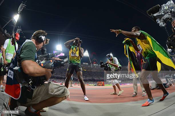 Usain Bolt of Jamaica takes photographs with one of the photographers' cameras as he celebrates winning gold in the Men's 200m Final next to Yohan...