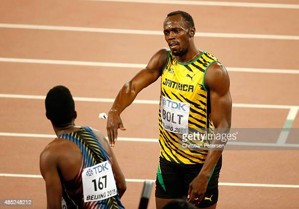 Usain Bolt of Jamaica talks with Miguel Francis of Antigua and Barbuda after competing in the Men's 200 metres semi-final during day five of the 15th...