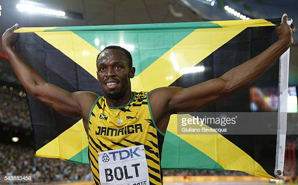 Usain Bolt of Jamaica with the Jamaican flag after winning the 100 m final