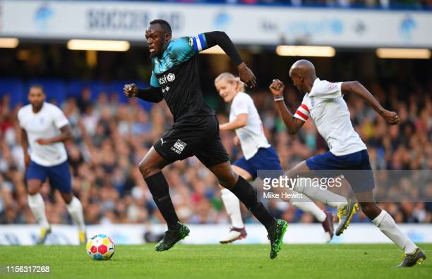 Usain Bolt of Soccer Aid World XI is chased by Sir Mo Farah of England during the Soccer Aid for UNICEF 2019 match between England and the Soccer Aid...