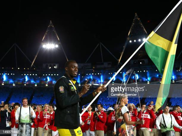Usain Bolt of the Jamaica Olympic athletics team carries his country's flag during the Opening Ceremony of the London 2012 Olympic Games at the...