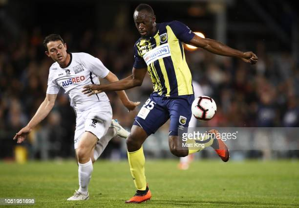 Usain Bolt of the Mariners beats Josh Symons of Macarthur South West United to score his first goal during the preseason friendly match between the...