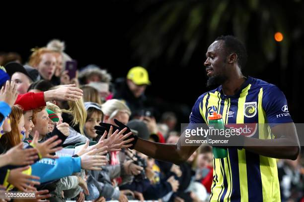Usain Bolt of the Mariners thanks Mariners fans after debuting in the preseason match between the Central Coast Mariners and Central Coast Football...