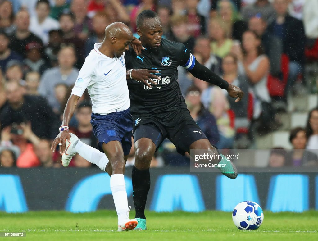 Usain Bolt of the Rest of the World and Sir Mo Farah of England battle for the ball during the Soccer Aid for UNICEF 2018 match between England and the Rest of the World at Old Trafford on June 10, 2018 in Manchester, England.