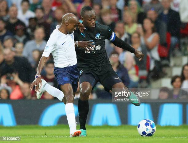 Usain Bolt of the Rest of the World and Sir Mo Farah of England battle for the ball during the Soccer Aid for UNICEF 2018 match between England and...