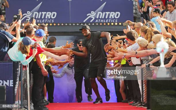 Usain Bolt of Usain Bolt's AllStar celebrates with supporters in the crowd as his team run onto the track during the Melbourne Nitro Athletics Series...