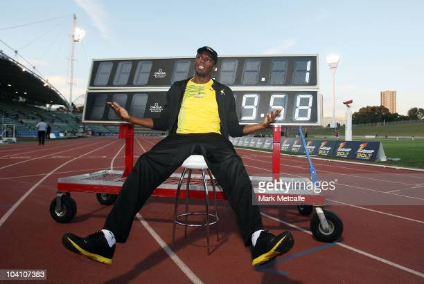 Usain Bolt poses in front of a scoreboard showing his world record time of 9.58 seconds during the Athletic Allstars Meet at Sydney Olympic Park...