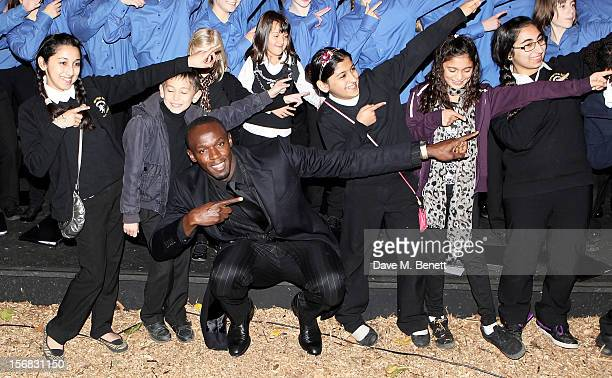 Usain Bolt poses with the children's choir at the Zeitz Foundation and ZSL Gala at London Zoo on November 22 2012 in London England