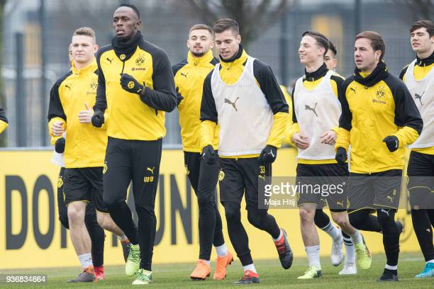 Usain Bolt runs with a players during a training of Borussia Dortmund on March 23 2018 in Dortmund Germany