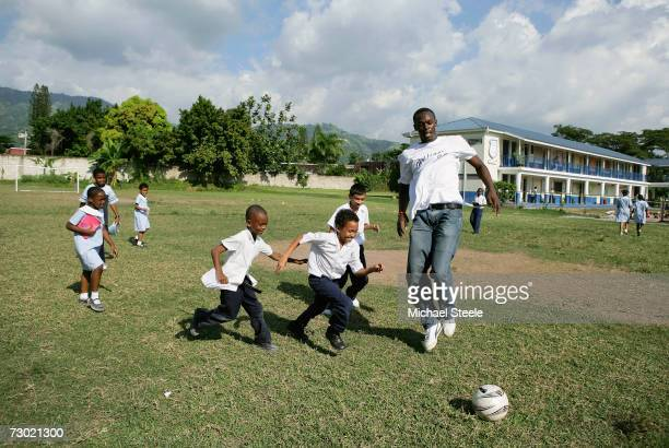 Usain Bolt the 200m and 400m sprinter plays football with schoolchildren during a visit to the Emmanuel Prep School on October 18 2006 in Kingston...