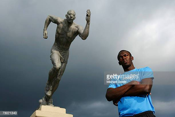 Usain Bolt the 200m and 400m sprinter poses in front of 'The Sprinter' statue at the National Stadium on October 17 2006 in Kingston Jamaica
