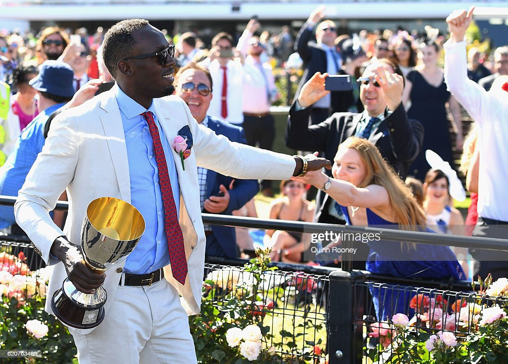 Usain Bolt walks down the track to present the trophy to the winner of the Crown Oaks on Oaks Day at Flemington Racecourse on November 3, 2016 in Melbourne, Australia.