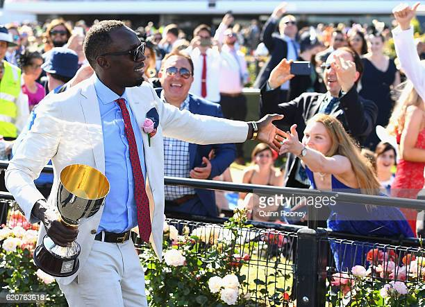 Usain Bolt walks down the track to present the trophy to the winner of the Crown Oaks on Oaks Day at Flemington Racecourse on November 3 2016 in...