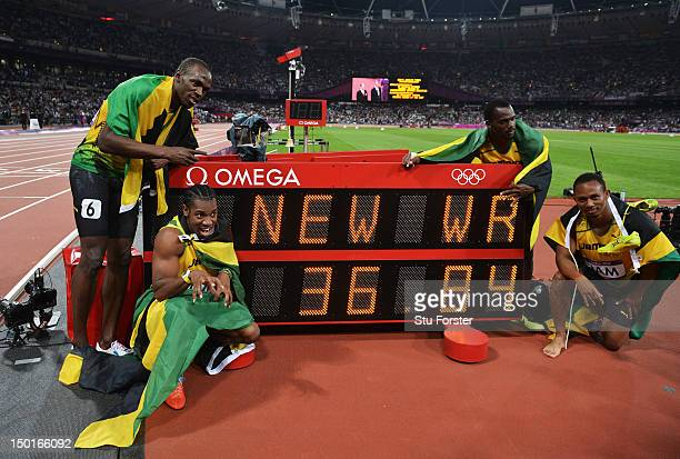 Usain Bolt, Yohan Blake, Michael Frater and Nesta Carter of Jamaica celebrate next to the clock after winning gold and setting a new world record of...