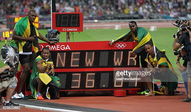 Usain Bolt, Yohan Blake, Nesta Carter and Michael Frater of Jamaica celebrate next to the scoreboard after winning the Mens 4 x 100m relay and...