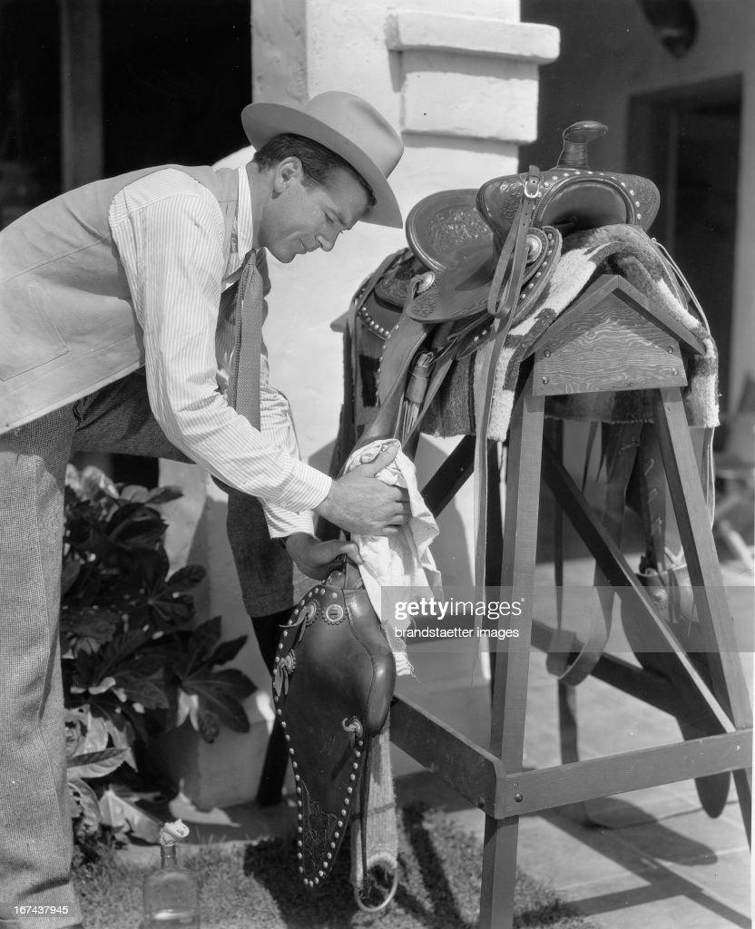 US-american actor Gary Cooper maintains his saddle. About 1930. Photograph. (Photo by Imagno/Getty Images) Der US-amerikanische Schauspieler Gary Cooperpflegt sein Sattelzeug. Um 1930. Photographie.