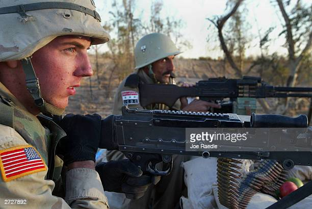 Army Specialist Robert Brown of Waco Texas of the 4th Infantry Division and Nativ Kazaum an Iraqi Civil Defense Corps soldier man their machine guns...