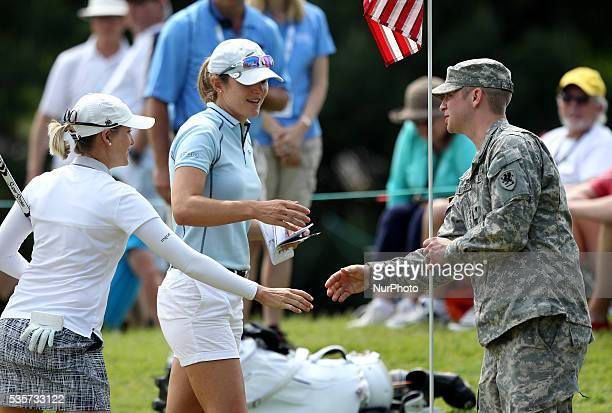 USArmy Specialist Zachary Loughrige greets Celine Herbin of France left and Sarah Jane Smith center of Caloundra Queensland at the ninth green where...