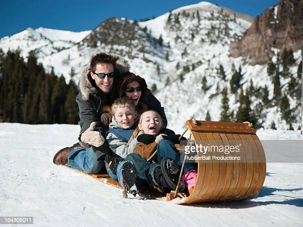 usa,utah,big cottonwood canyon,parents with children (8-9,10-11) sledding down snowy hill - tobogganing stock pictures, royalty-free photos & images