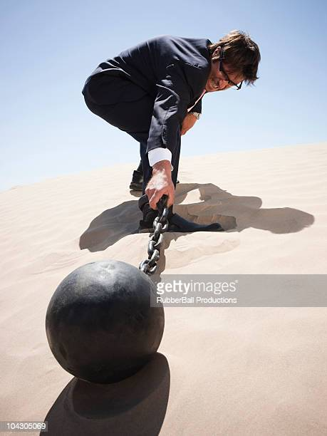 USA,Utah,Little Sahara,Businessman pulling ball and chain on the desert