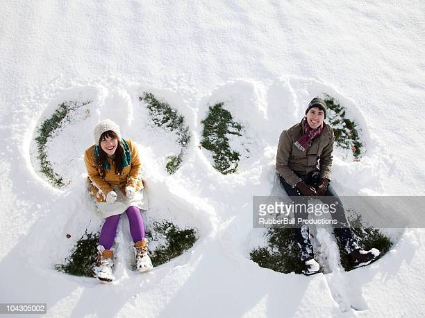 USA,Utah,Orem,Young couple sitting in snow making snow angel
