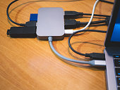 usb type-c hub connected to laptop with lot of cables connected for peripheral computer device equipment