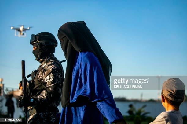 Backed Syrian Democratic Forces escort a fully veiled woman and a child in the northern Kuridish-Syrian city of Qamishli as Uzbek women and children...